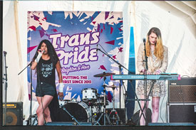 Powderpaint perform on stage in front of a Trans Pride banner. Photo credit: Lollo Popper